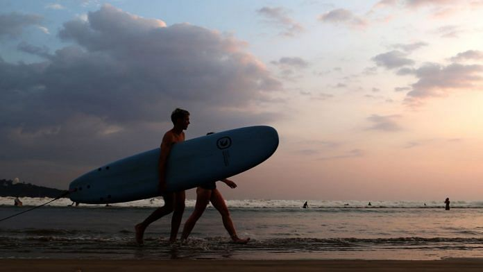 Tourists with a surfboard walk along Dewata Beach in Galle, Sri Lanka | Buddhika Weerasinghe | Bloomberg