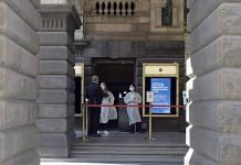 Medical workers in protective gear at the entrance to a vaccination hub in the Town Hall in Melbourne, Australia, earlier this month. | Bloomberg