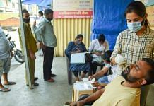 A medic takes a swab sample of a man for the Covid-19 test, at APMC vegetable market in Navi Mumbai, on 16 October 2021 | PTI