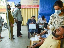 A medic takes a swab sample of a man for the Covid-19 test, at APMC vegetable market in Navi Mumbai, on 16 October 2021   PTI