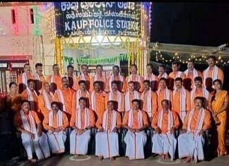 Police personnel dressed in saffron pose outside the Kaup police station in Udupi on the festival of Ayudha Pooja last week   Photo: Twitter   @siddaramaiah