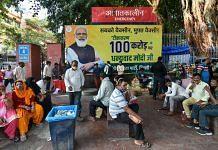 People sit near a poster commemorating India's 1 billion Covid-19 vaccine dose milestone at RML Hospital in New Delhi, on 21 October 2021 | PTI
