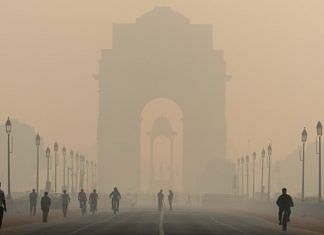 Pedestrians walk along Rajpath boulevard as India Gate monument stands shrouded in smog in New Delhi, India| Bloomberg