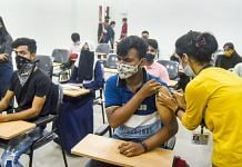 A health worker inoculates a dose of Covid-19 vaccine to college students, during vaccination drive in Mumbai on 25 October 2021| PTI