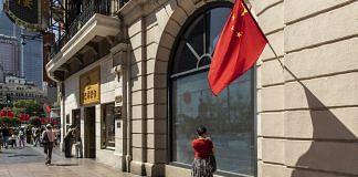 A China flag outside a shop in Nanjing Road East in Shanghai | Photo: Qilai Shen | Bloomberg