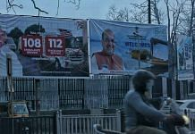 A man rides by a banner welcoming Amit Shah. | Photo: Praveen Jain | ThePrint